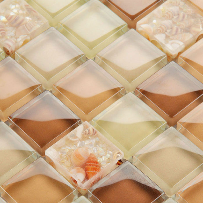 glass mosaic tile backsplash, in glossy brown, orange and light yellow, containing small conch seashells, in similar colors