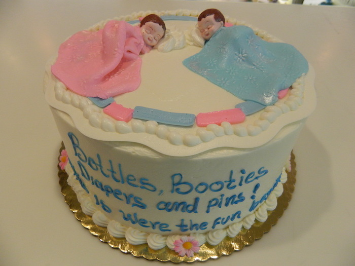 couple of sleeping baby figurines, one covered in a pink blanket, and one in a blue blanket, on top of a white cake, twin baby shower cakes, decorated with a message, done in blue frosting