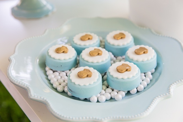 ornate pale blue plate, containing seven pastries, decorated with white, doily-like fondant shapes, and tiny gold-colored baby onesies, onesie cake ideas, white edible pearls