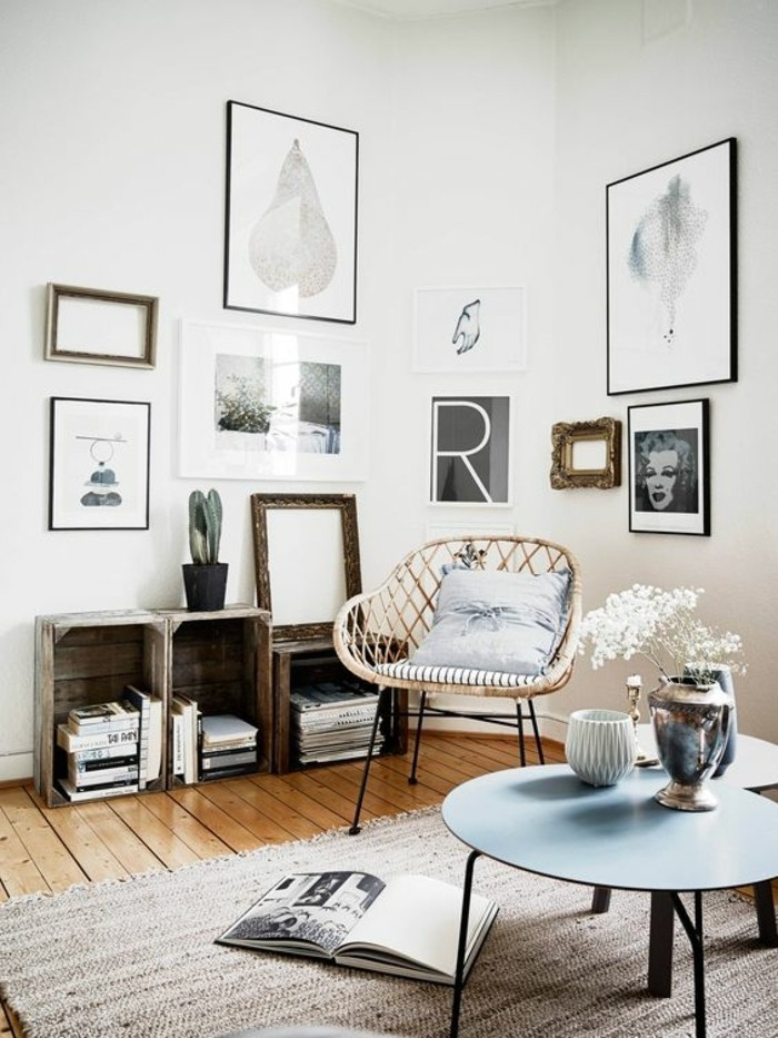 old wooden crates, transformed into bookshelves, inside a nordic style room, with wooden floor, beige rug and a wicker chair