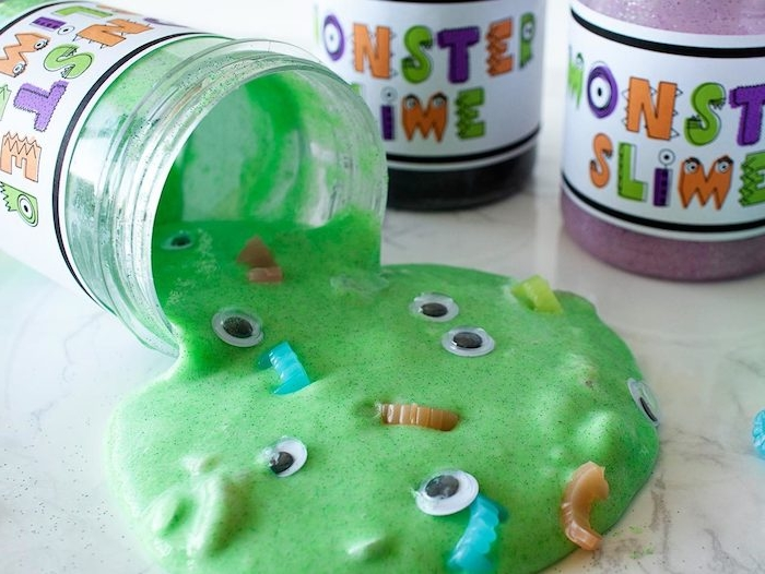 monster slime written in colorful letters, on the labels of three small jars, containing goo in different colors, one jar is turned on its side, with green goo, decorated with eye stickers and plastic fangs seeping out