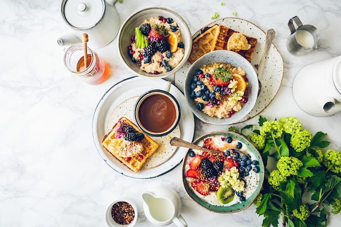 breakfast menu ideas, three bowls of porridge, topped with assorted fruit, placed near or on two plates with waffles, honey and teapots, coffee cup and milk jugs