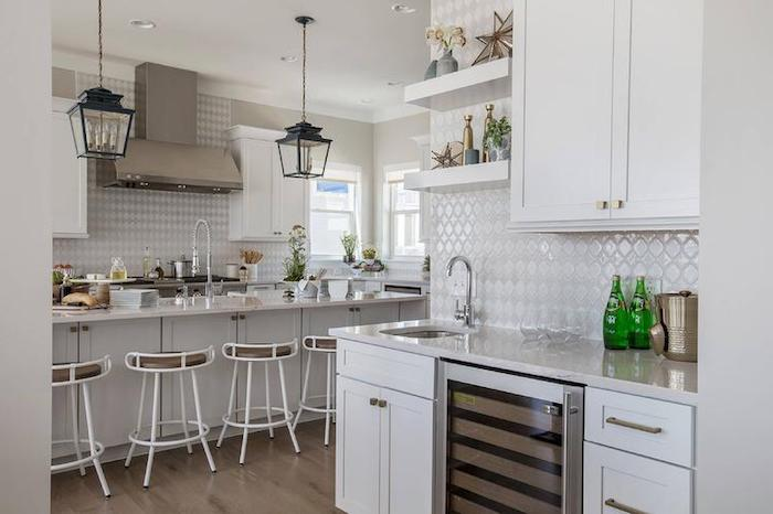 lantern-style lamps hanging from the ceiling, white kitchen cabinets, glossy off-white arabesque backsplash, several stools and a counter top