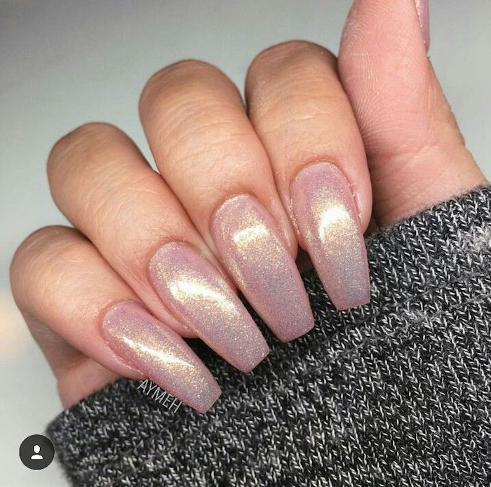 pearly shimmering pink nails, long and oval, with square tips, attached to a hand, holding a grey, salt and pepper knitted sleeve