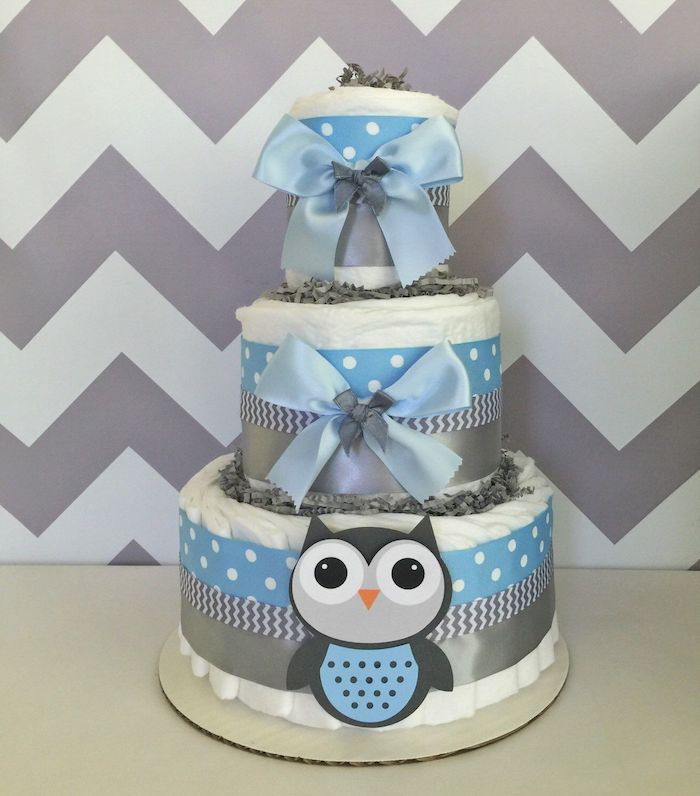 ribbons in pale blue and grey, plain and patterned, on a white diaper cake, with a little owl decoration, owl baby shower cake, grey and white zigzag pattern on the wall behind
