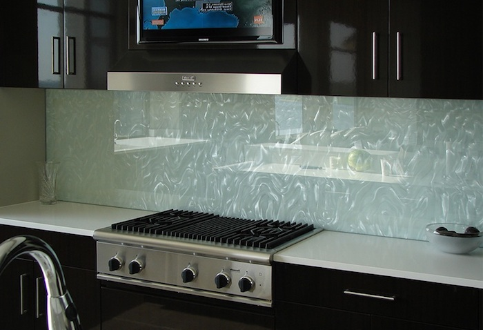 water-effect glass backsplash, in pale blue, with glittering silver details, near glossy and smooth, black kitchen cabinets, and a white counter top