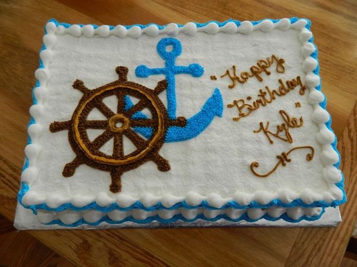steering wheel of a ship, in brown and beige, and a blue anchor, painted in frosting, on a white rectangular cake, nautical baby shower cakes