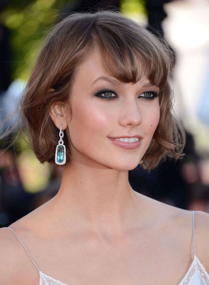 karlie kloss with a short, wavy brunette bob, wearing a white strappy top, dark eye make up, and a glossy pale pink lipstick, short haircuts for thin hair