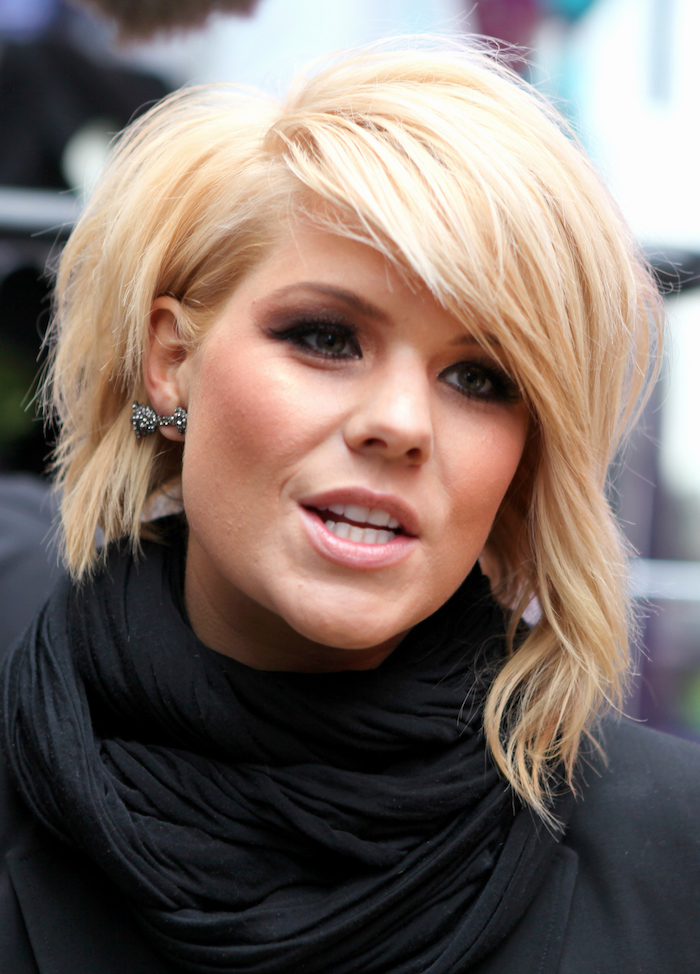 talking blonde woman, with an asymmetrical wavy bob, with added volume and waves, black top and matching scarf, nude pink lipstick, and dark eye make up