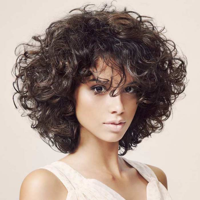 dark brunette voluminous curly hair, shoulder length with bangs, hairstyles for short curly hair, on slim young woman, with dark eyes, discrete make up and white top