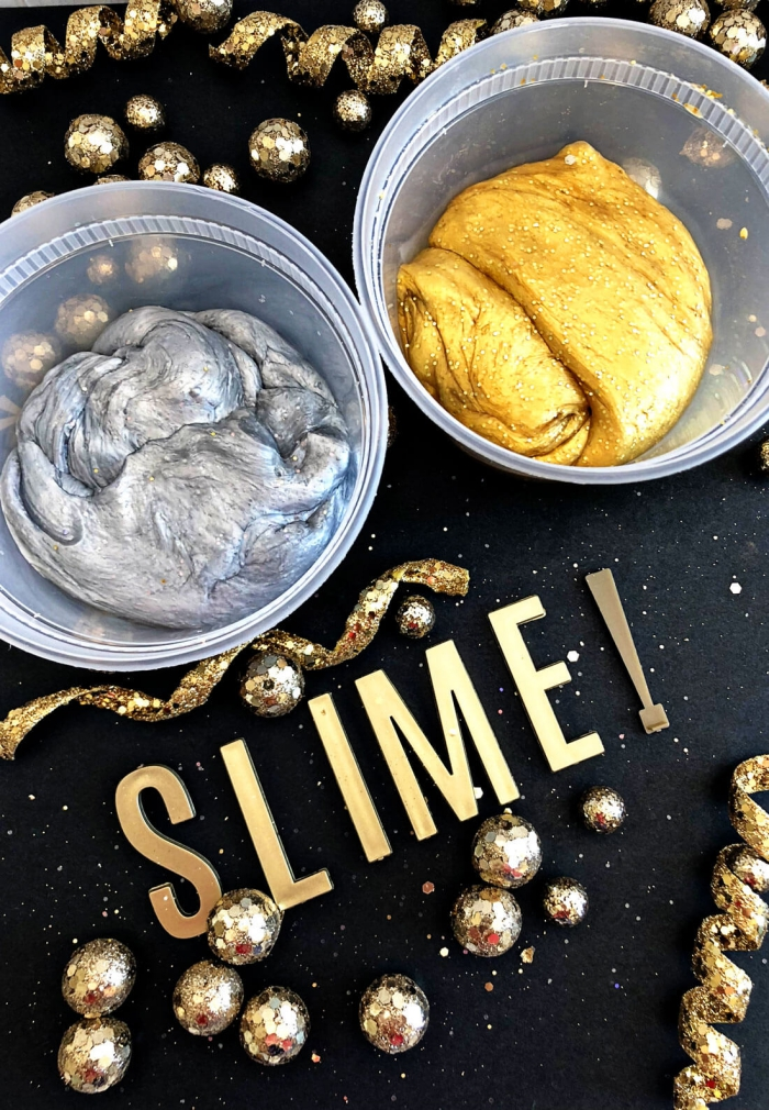 how to make slime with borax, two plastic pots, containing silver and gold metallic slime, placed on a black surface, near some glittering golden decorations