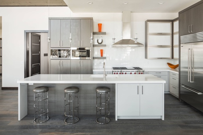 stools in metallic grey, near a white counter top, inside a kitchen with grey, and metallic silver cabinets, with splashes of orange, white subway tile