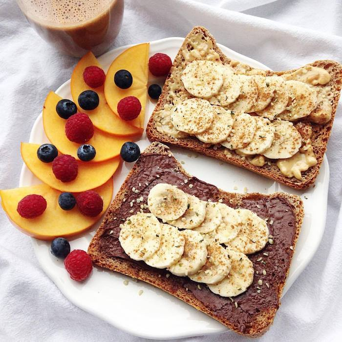 toast with different spreads, chocolate and peanut butter, topped with banana slices, cinnamon and sesame seeds, peach slices and berries