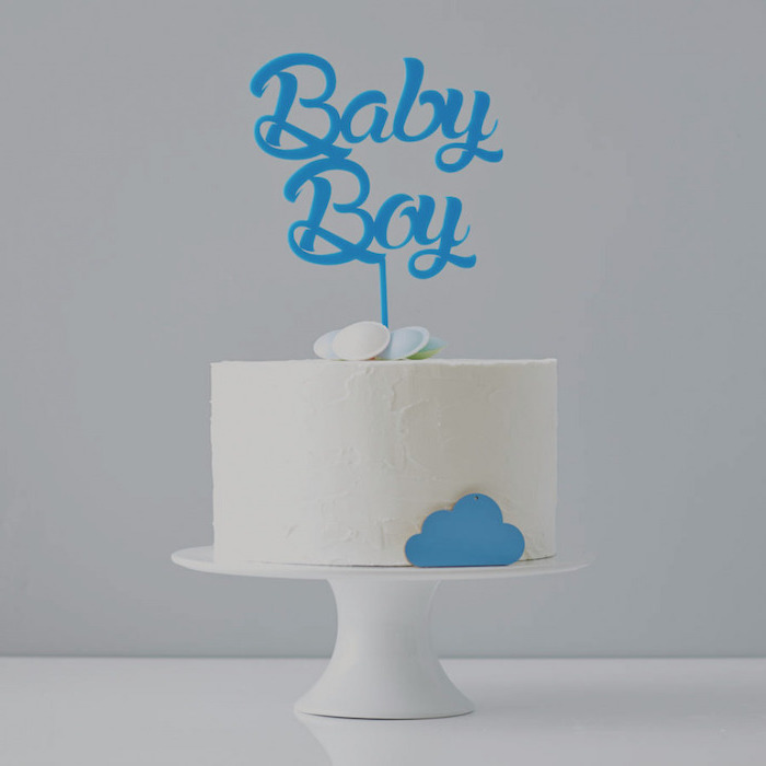 minimalistic cake with white frosting, decorated with several flying saucer candies, and a little blue cloud, on a white cake stand, with a blue topper, reading baby boy