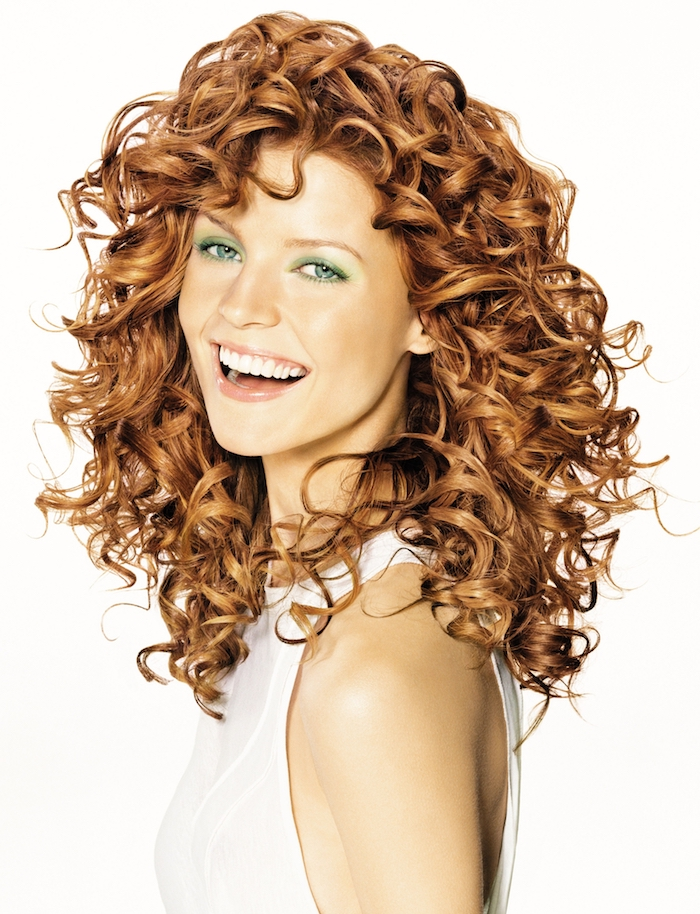 hairstyles for curly hair, laughing woman with green eyes, and pale green eye make up, wearing a white sleeveless top, light chestnut shoulder length curls