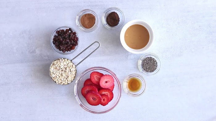 eight round containers of various sizes, with strawberry slices, raisins and rolled oats, honey and seeds, and various condiments