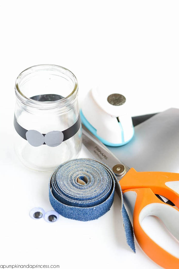 denim-colored washi tape, a pair of scissors in white and orange, small clear glass jar, decorated with paper, googly eye stickers, materials for minion slime container
