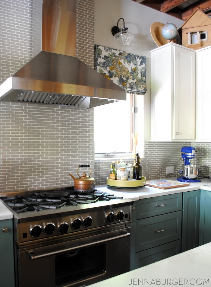 teal and white cabinets and drawers, in a kitchen with a metal oven, and a matching extractor hood, small grey subway tile pattern on the wall