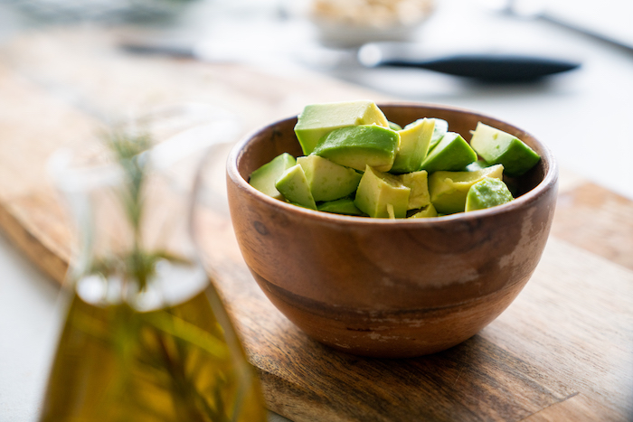 chopped avocado in small wooden bowl, placed on wooden board, basil pesto recipe