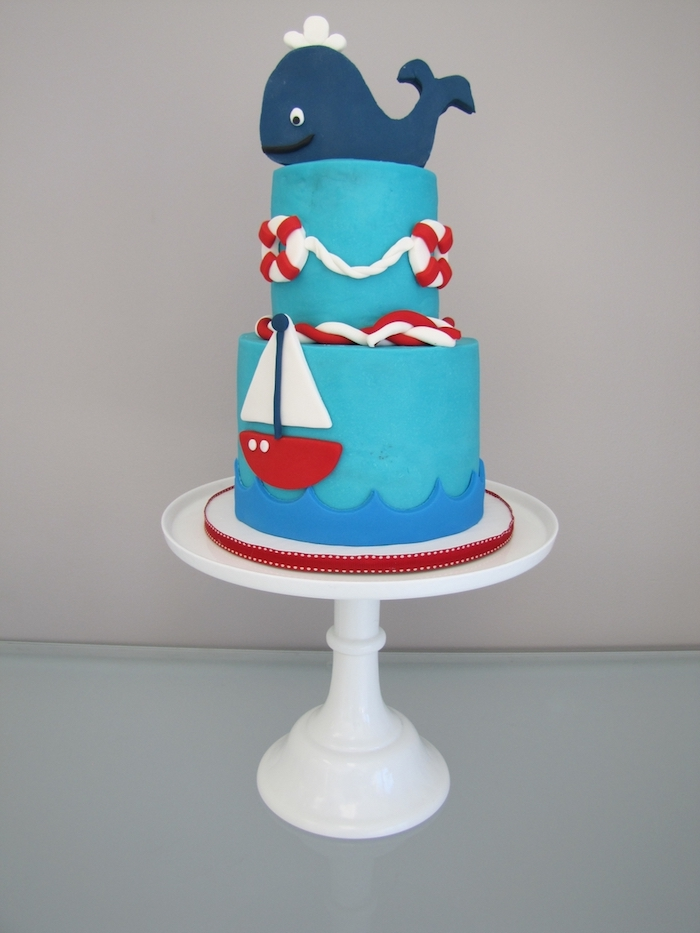 nautical baby shower cakes, smiling whale figurine, made from dark blue fondant, topping a turquoise cake, decorated with red and white details, sailing boat and lifebelts