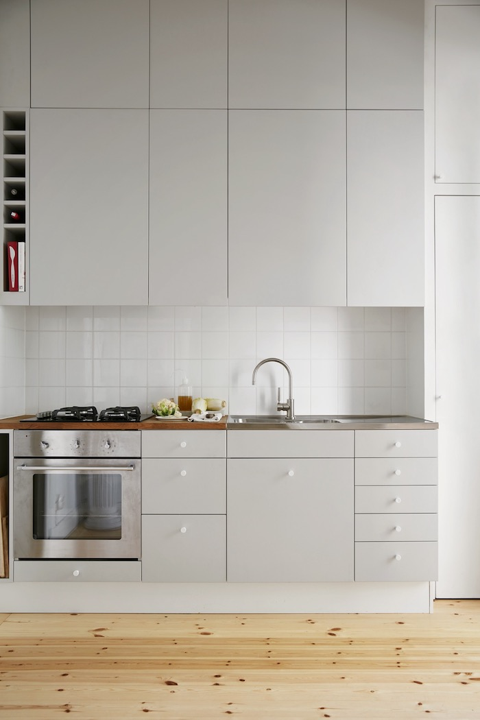 square tiles on a white kitchen backsplash, in a room with white cabinets, shiny metal oven, and a beige wooden floor