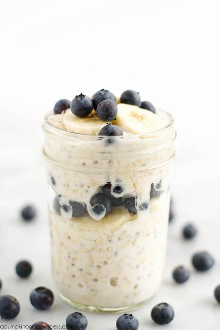overnight oats served in a glass jar, with blueberries and banana slices, what is a healthy breakfast, on a white surface with other blueberries