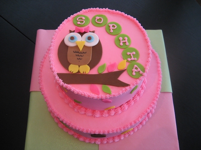 bubblegum pink two-layered cake, decorated with brown owl figurine, made from fondant, and green buttons, with pale pink frosting, spelling out the name sophia, owl baby shower cake