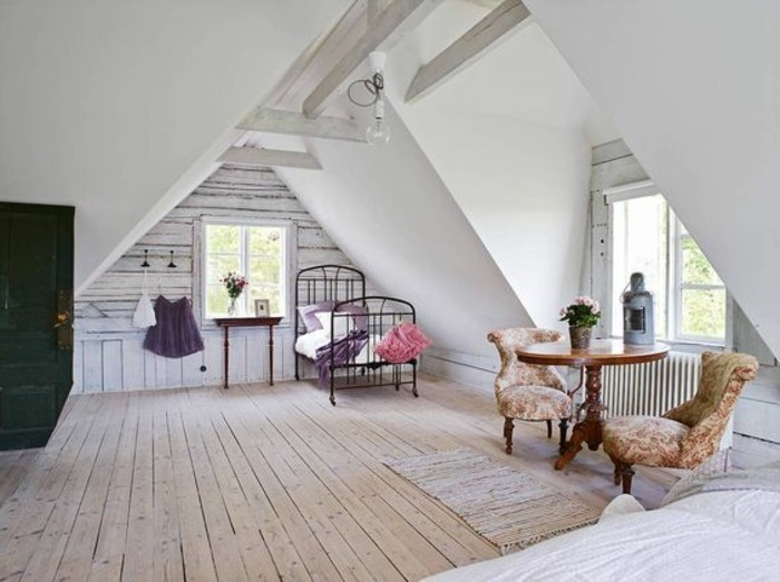 vintage-inspired furniture, inside a spacious attic room, room design, black wrought iron bed, two retro armchairs, ornate wooden coffee table