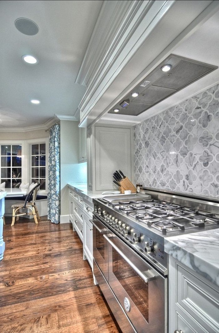 large room with a brown wooden floor, marble counter tops, grey arabesque backsplash, two ovens and off-white kitchen cabinets