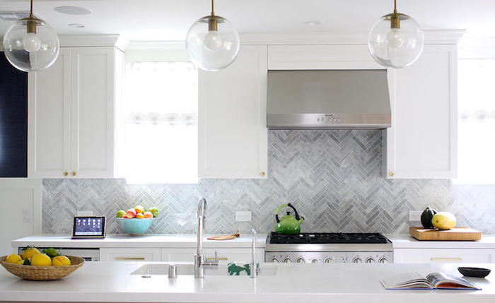 round clear glass lamps, hanging over a white counter top, with an inbuilt sink, in a bright kitchen, with grey herringbone backsplash, and white cabinets
