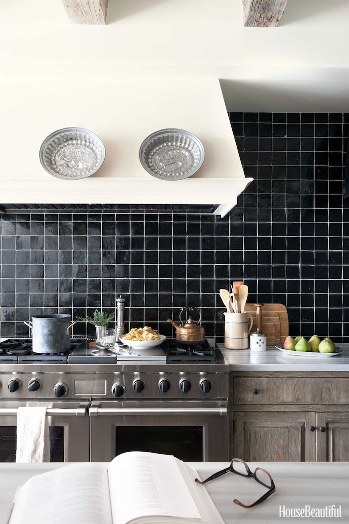 vintage style kitchen, with a wall covered in smooth, square black tiles, grayish-brown cabinets, two ovens with stoves