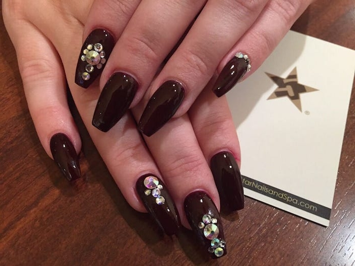 very dark cherry red nail polish, decorating the eight visible nails of two hands, ballerina nail shape, with rhinestones in different sizes