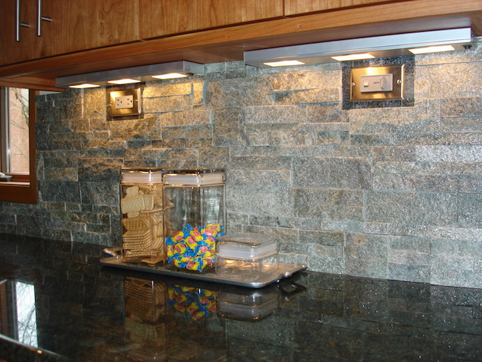 biscuits and candy, in two glass containers, on a black counter top, grey stacked stone backsplash, wooden kitchen cabinets