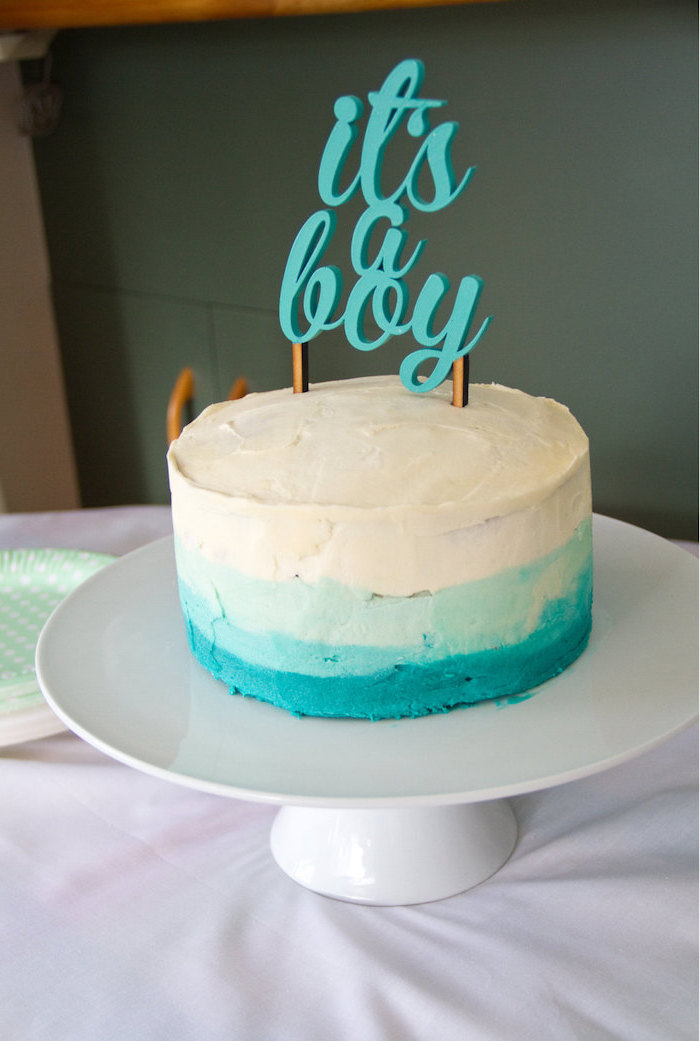 it's a boy written in turquoise, on a topper, decorating a white and turquoise, ombre effect cake, placed on a white ceramic cake stand