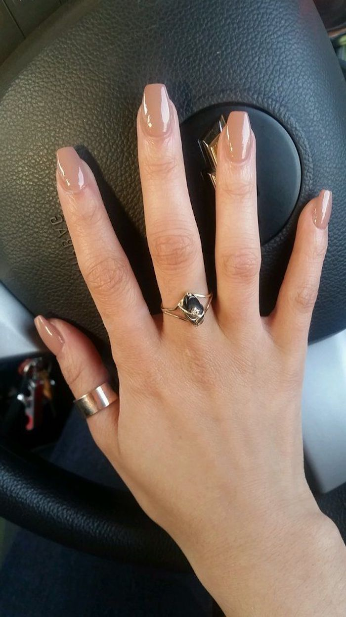 medium length nude coffin nails, on a hand with outstretched fingers, and two golden rings, resting on a black steering wheel of a car