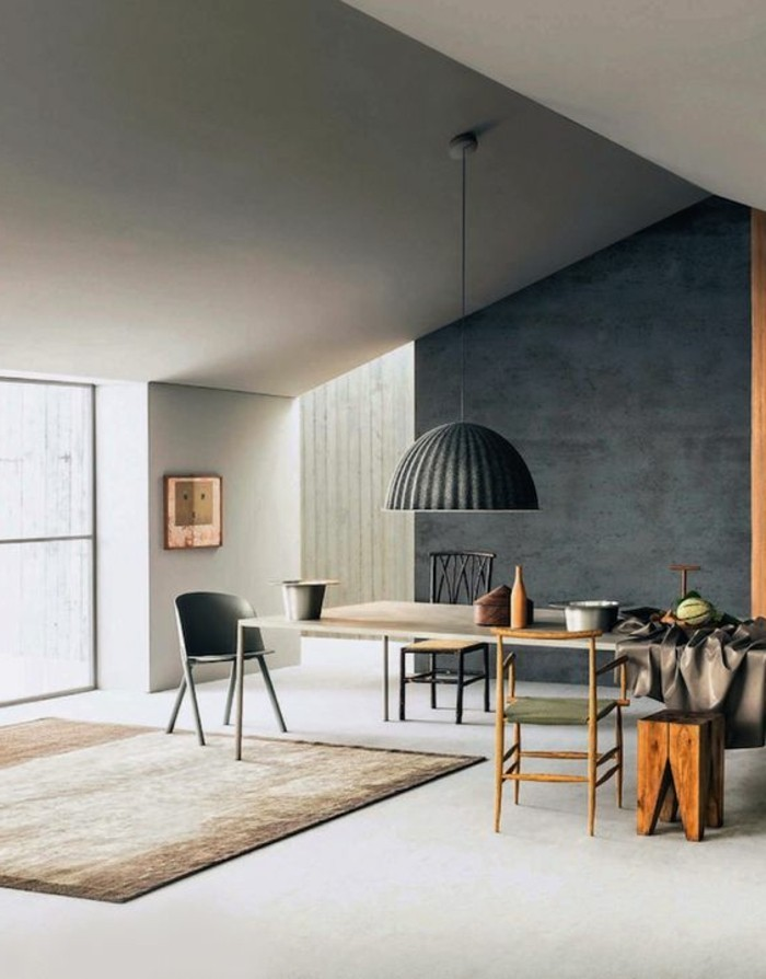 dining table with three mismatched chairs and a stool, inside a room with a sloped ceiling, white floor and light grey walls, a dark grey accent wall