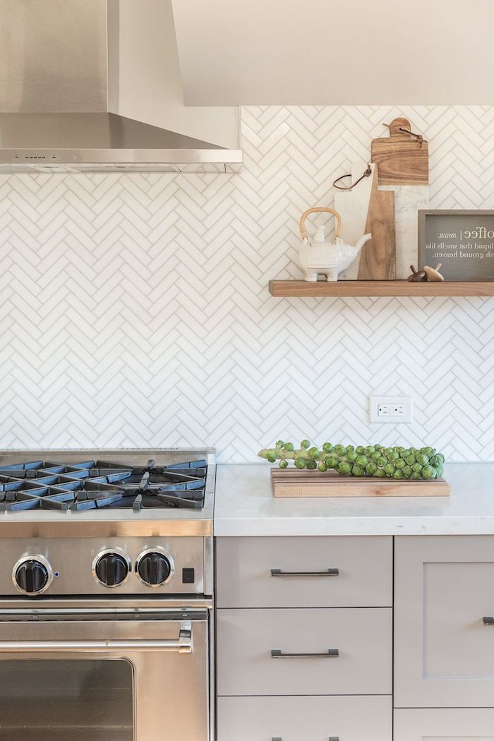 herringbone backsplash in white, with cream-colored joints, near a metal extractor hood, placed over a stove, creamy grey cabinets