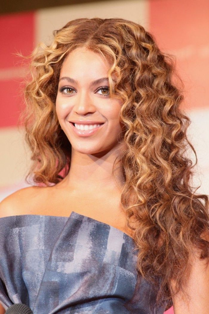 long curly hairstyles, beyonce smiling in a strapless, grey and blue top, with long curly hair, in blonde and light brunette hues