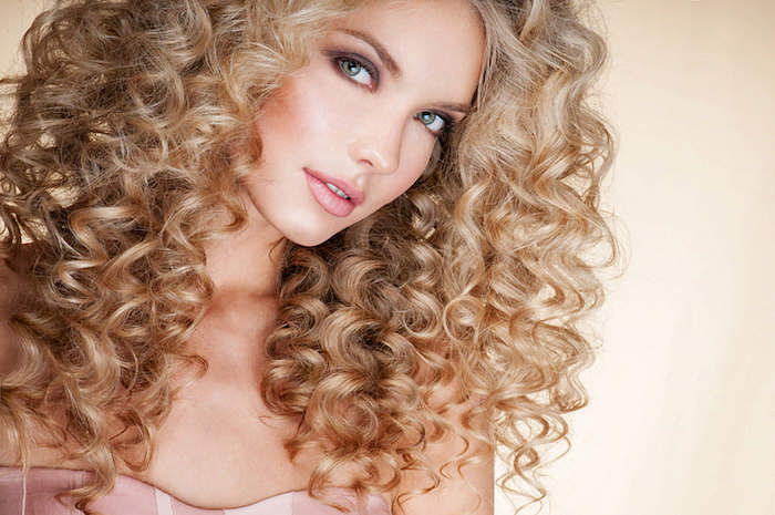 light blonde voluminous curly hair, shoulder length with slightly darker tips, hairstyles for curly hair, worn by young, blue-eyed girl with purple eye make up, and pink lipstick