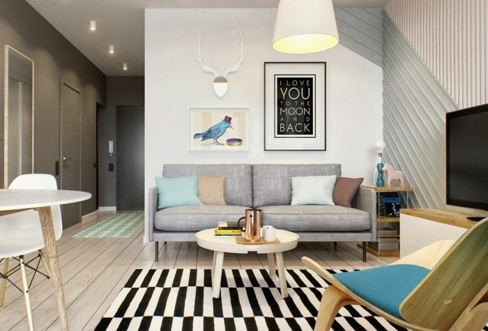bauhaus style room, with a pale grey sofa, a striped black and white rug, and a small coffee table, how to decorate a living room, framed artwork and modern chairs