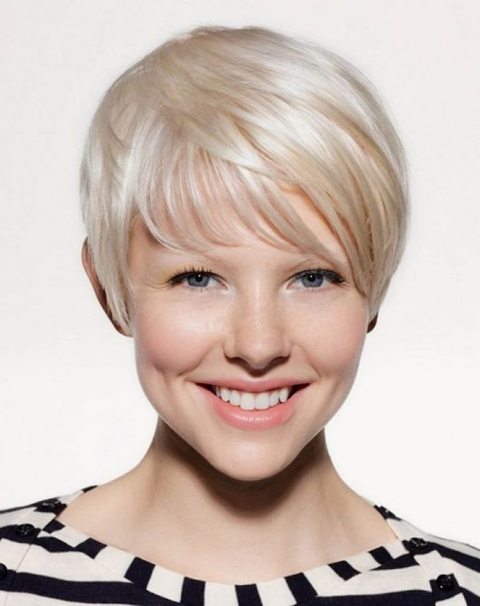 dimpled smiling woman, with platinum blonde messy bob, and side bangs, wearing a striped black and white top