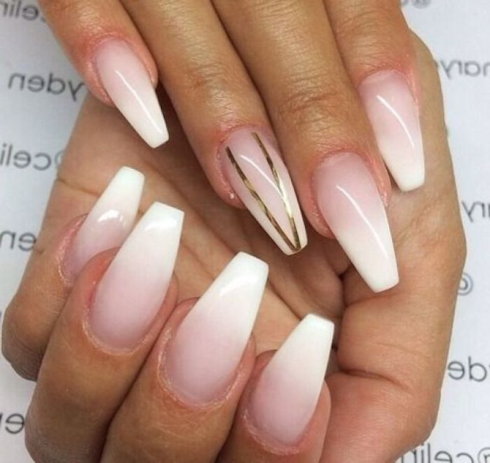 french-style ombre-effect nude coffin nails, with pale pink base, and white tips, one of the nails is decorated with two gold stripes