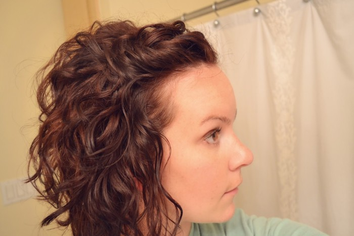 soft curly dark brunette hair, styled and twisted backwards, short haircuts for curly hair, worn by woman in profile, wearing pale turquoise top