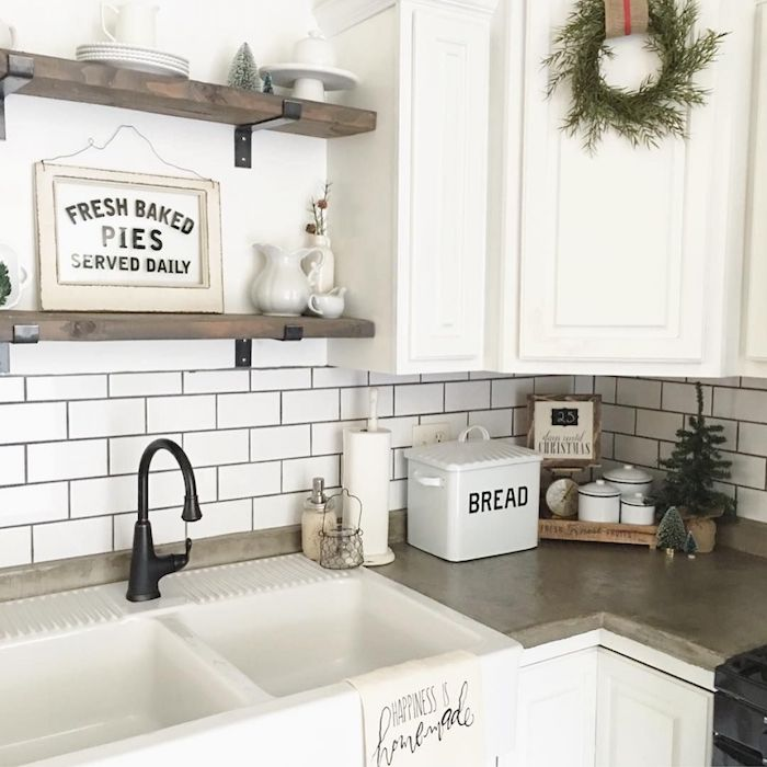 vintage style kitchen, with a beige counter top, retro-inspired white sink, and dark antique faucet, white subway tile pattern, and white cabinets