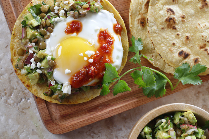 lentils and avocado, veggies and salsa, and a sunny side up runny egg, on a breakfast taco, more tacos and chutney, and a sprig of cilantro
