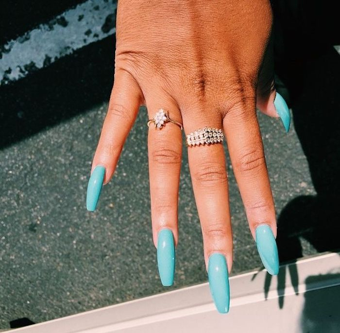 encrusted golden rings, worn on the ring and middle fingers of a tan hand, with long coffin nails, in turquoise blue
