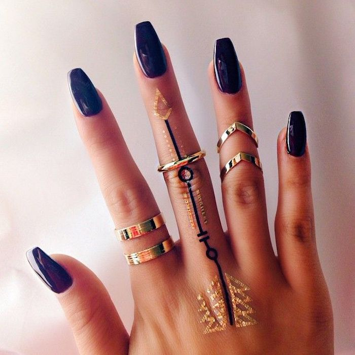 temporary hand tattoos, in black and gold, on a hand with acrylic nail shapes, painted in a smooth and glossy, dark violet nail polish