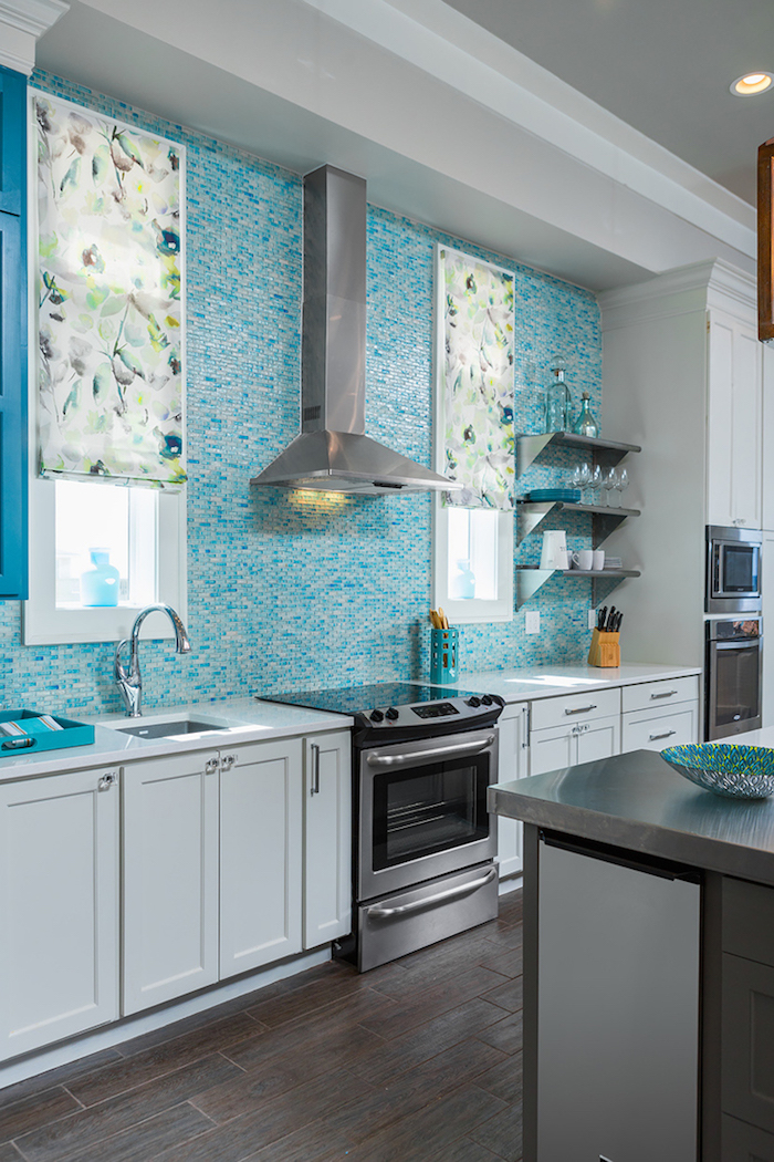 window blinds in white, with floral motifs, in a kitchen with white cabinets, teal blue and white glass mosaic tile backsplash, and dark wooden floor