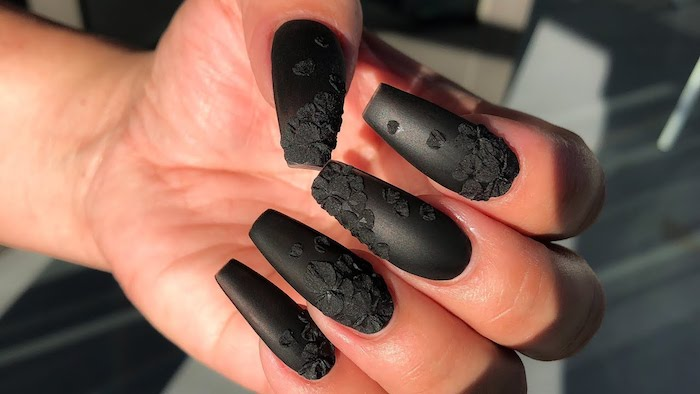 3D effect black acrylic flowers, decorating long nails, painted with black nail polish, coffin nail designs, on a hand with folded fingers