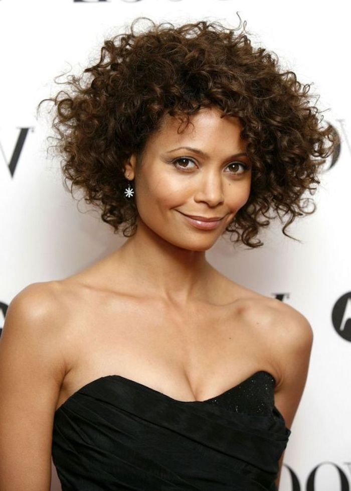 bustier strapless top in black, worn by thandie newton, smiling with discrete make up, voluminous curly dark brunette hair, in short curly bob